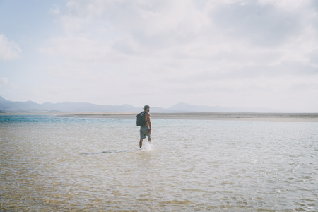 Handsome muscular bearded man walking on the sea shore at sunrise with backpack