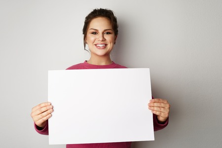 Beautiful smiling young women with banner sign with white blank empty paper billboard with copy space for text over gray background
