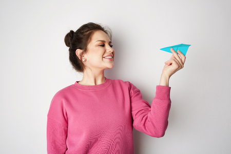 Young smiling woman holding hand model blue paper air plane. Design of travel concept with plane on empty gray color background Stock Photo