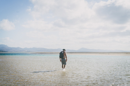 Young muscular bearded man walking on the sea shore at sunrise with backpack