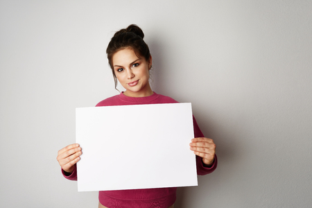 Pretty young woman holding empty blank board isolated on the gray background