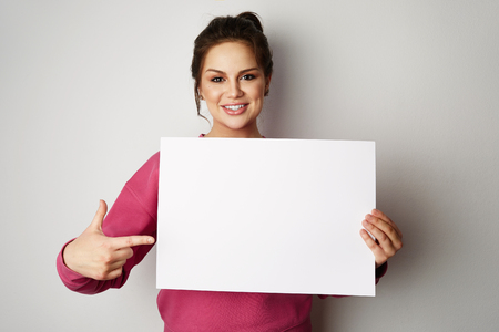 Pretty smiling woman holding empty blank board isolated on the gray background Stock Photo