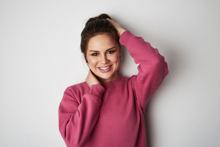 Beautiful handsome women with big brown eyes wearing pink hoody and smiling at camera over empty white background.Model with light nude make-up, studio background, copy paste text space.