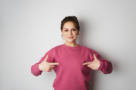 Beautiful smiling hipster girl wearing pink hoody and pointing finger with space for your logo or design. Mock-up of pink hoody on white empty wall in the background. Copy paste text space