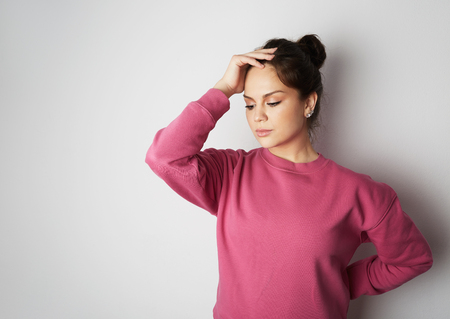 Young girl in pink hoody with a severe headache with the hands in the head over white empty wall on background. Beauty and healthcare concept Stock Photo