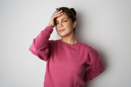 Handsome young woman with big brown eyes wearing pink hoody and holding hand on head over empty white background.Model with light nude make-up, studio background, copy paste text space.
