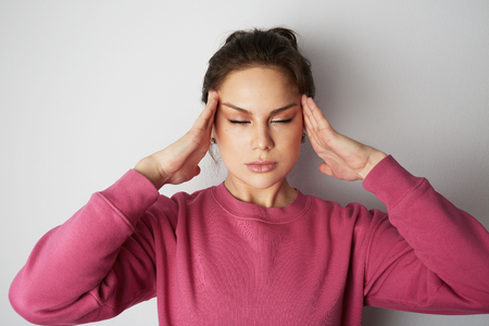 Young woman in pink hoody with a severe headache with the hands in the head over white empty wall on background. Beauty and healthcare concept Stock Photo
