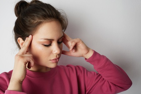 Handsome woman in pink hoody with a severe headache with the hands in the head over white empty wall on background. Beauty and healthcare concept Stock Photo