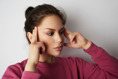 Beautiful woman in pink hoody with a severe headache with the hands in the head over white empty wall on background. Beauty and healthcare concept