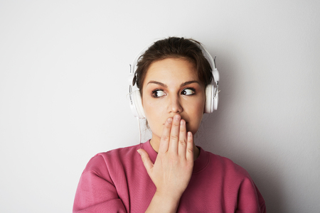 Fashion pretty cool girl in white headphones listening to music wearing colorful pink hoody over white background