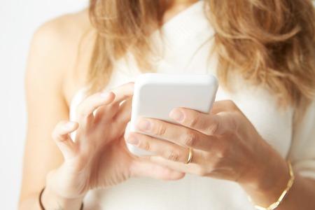 Beautiful woman using electronic smart phone over empty white background Stock Photo