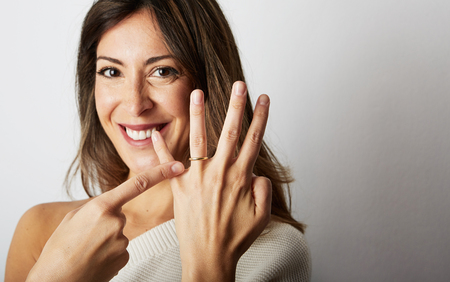 Jewellery is best friend of women concept. Attractive european girl with long dark hair in stylish clothes smiling and holding hand on hip while showing trendy wedding ring