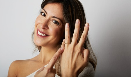 Happy european girl with long dark hair in stylish clothes smiling and holding hand on hip while showing trendy wedding ring over empty white wall background.Copy paste text message space. Close-up Stock Photo