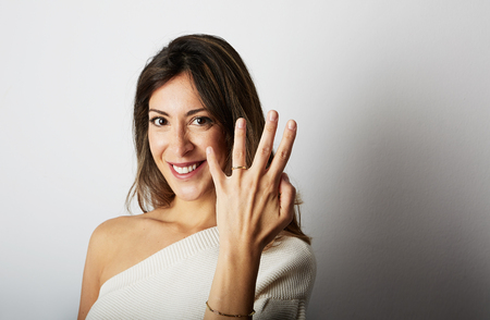 Happy european girl with long dark hair in stylish clothes smiling and holding hand on hip while showing trendy wedding ring over empty white wall background.Copy paste text message space
