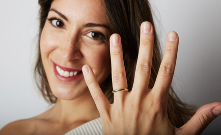 Jewellery is best friend of women concept. Happy caucasian woman with long dark hair in stylish clothes smiling and holding hand on hip with trendy wedding ring.Closeup