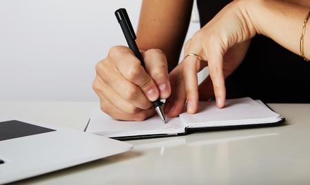 Beautiful Female hands write pen in a notebook of tasks and goals to work on a wooden table.The hands of a business woman writing on a notepad with a pen