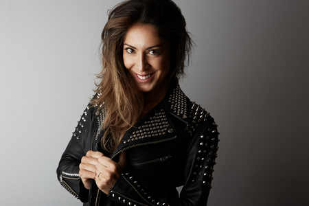 Fashion photo of a beautiful smiling brunette woman wearing leather jacket with dark long hair posing over white empty background.Positive human emotions, reaction, gestures.Fashion female concept