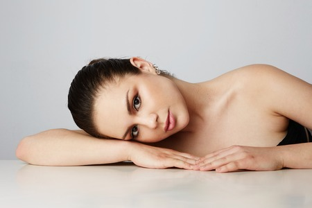 Beautiful women with big brown eyes and dark eyebrows relaxing over empty gray studio background.Model with light nude make-up.Copy paste space,close up.Healthcare skin concept Stock Photo