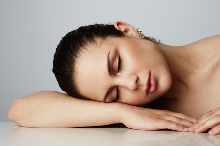 Beautiful women with dark eyebrows sleeping with over empty gray studio background.Model with light nude make-up.Copy paste text space,close up.Healthcare skin makeup concept Stock Photo