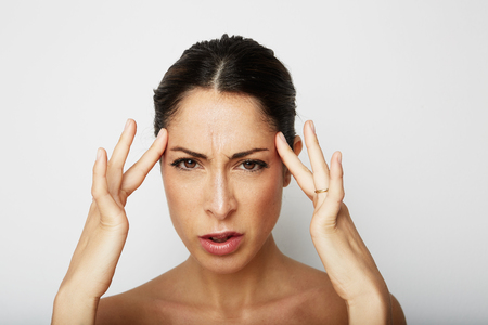 Portrait of Beautiful young woman with a severe headache with the hands in the head over white empty wall on background. Beauty and healthcare concept
