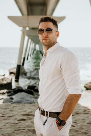 Young handsome man walking at the sea, enjoy summer season. Relax caucasian young man looking away at sunny day. Vertical