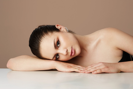 Beautiful woman with big brown eyes and dark eyebrows relaxing over empty color studio background.Model with light nude make-up.Copy paste space,close up.Healthcare skin makeup concept