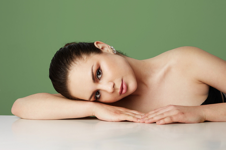 Beautiful woman with big brown eyes and dark eyebrows relaxing over empty green studio background.Model with light nude make-up.Copy paste space,close up.Healthcare skin concept