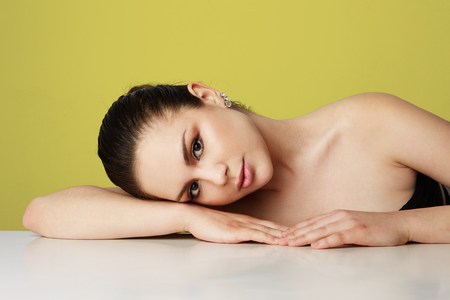 Beautiful young woman with big brown eyes and dark eyebrows relaxing over empty yellow studio background.Model with light nude make-up.Copy paste space,close up.Healthcare skin concept