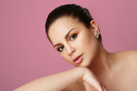 Young girl with big brown eyes and dark eyebrows looking over empty pink colored studio background.Model with light nude make-up.Copy paste text space,close up.Healthcare skin makeup concept