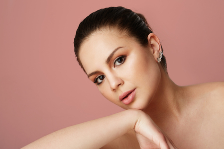 Young girl with big brown eyes and dark eyebrows looking over empty beige colored studio background.Model with light nude make-up.Copy paste text space,close up.Healthcare skin makeup concept