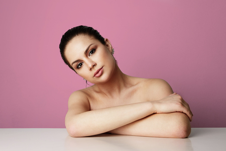 Beautiful young girl with big brown eyes and dark eyebrows sitting at wooden desk over empty pink colored studio background.Model with light nude make-up.Healthcare skin makeup concept.