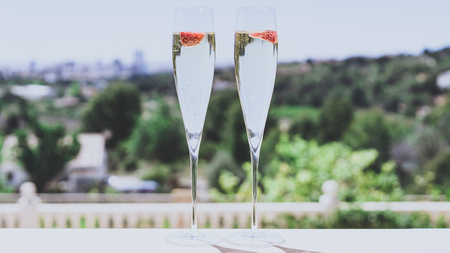 Two champagne glasses with strawberry on sunny terrace outdoor patio overlooking green trees at summer day outside of the city Stock Photo