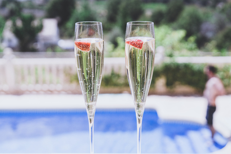 Two champagne glasses with strawberry on sunny terrace outdoor patio overlooking swimming pool at summer day outside of the city.Relaxing holidays concept Stock Photo