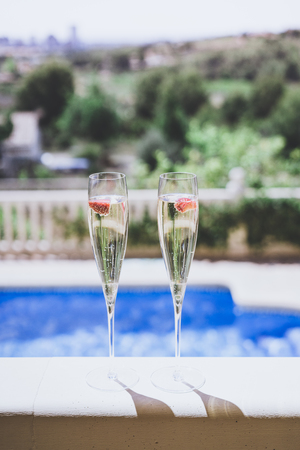 Two champagne glasses with strawberry on sunny terrace outdoor patio overlooking swimming pool at summer day outside of the city.Vertical Stock Photo