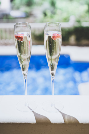 Two champagne glasses with strawberry on sunny terrace outdoor patio overlooking swimming pool at summer day outside of the city.Closeup view.