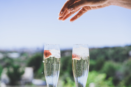 Female hand throwing ice into a glasses champagne with strawberry inside on sunny terrace overlooking swimming pool at summer day outside of the city.Beauty holidays fashion concept