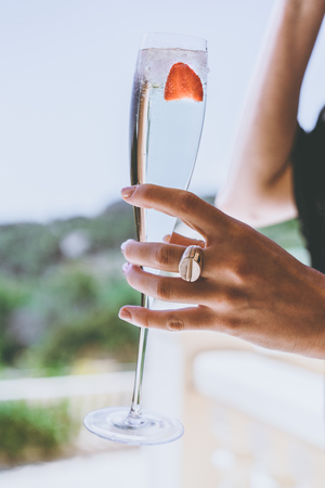 Female woman holding hand glasses champagne with strawberry inside on sunny terrace overlooking swimming pool at summer day outside of the city.Beauty holidays fashion concept.Vertical