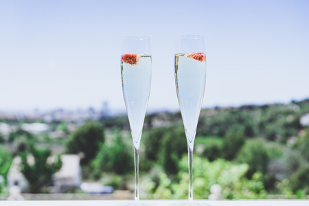 Two champagne glasses with strawberry on sunny terrace outdoor patio overlooking clean blue sky at summer day outside of the city