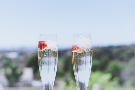Closeup view of Two beautiful champagne glasses with strawberry on sunny terrace outdoor. Summer day outside of the city