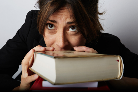 Young overwhelmed woman studying hard. Tired, stressed and overworked young student.Female model between a huge pile of books.Closeup view Stock Photo