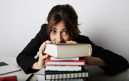 Young overwhelmed woman studying hard. Tired, stressed and overworked young student.Female model between a huge pile of books Stock Photo