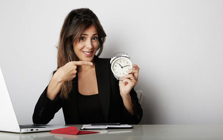 Pretty woman holding white vintage alarm clock and showing hand OK symbol over empty gray color background Stock Photo