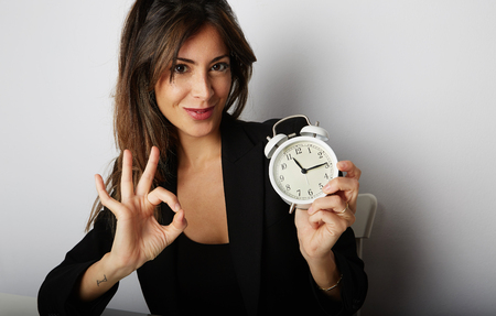 Pretty woman holding white vintage alarm clock and showing hand OK symbol over empty gray color background. Cropped.