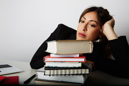 Young overwhelmed girl studying hard. Tired, stressed and overworked young woman student.Female model between a huge pile of books.Closeup view
