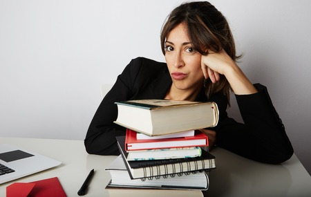 Young overwhelmed girl studying hard. Tired, stressed and overworked young woman student.Female model between a huge pile of books