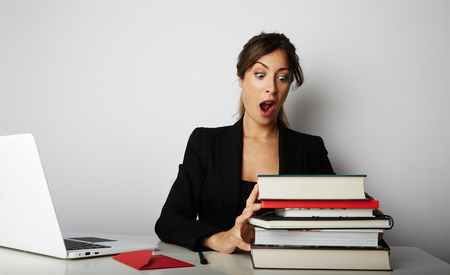 Young overwhelmed girl working hard. Young woman student shock of many books.Female model front of huge pile of books