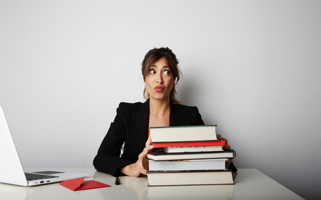 Young overwhelmed woman working hard. Young woman student shock of many books.Female model front of huge pile of books Stock Photo