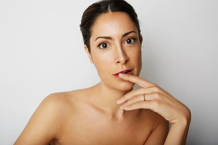 Portrait of handsome beauty woman with big brown eyes and dark eyebrows looking away over empty white background.Model with light nude make-up.Copy paste space,close up.Healthcare skin concept