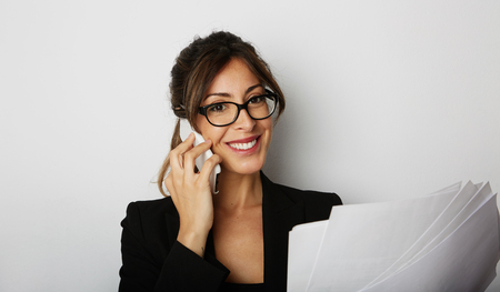 Young caucasian happy female woman using mobile phone sitting at the table over empty white studio background Stock Photo
