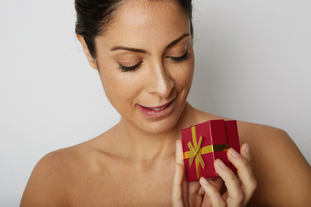 Fashion glamour photo of a beautiful brunette woman with dark hair holding hand red gift box over white empty background.Positive human emotions, reaction, gestures